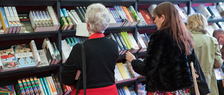 Two people browsing bookshelves at the Festival Bookshop